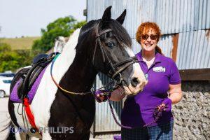 A Long Furlong RDA volunteer standing with a horse